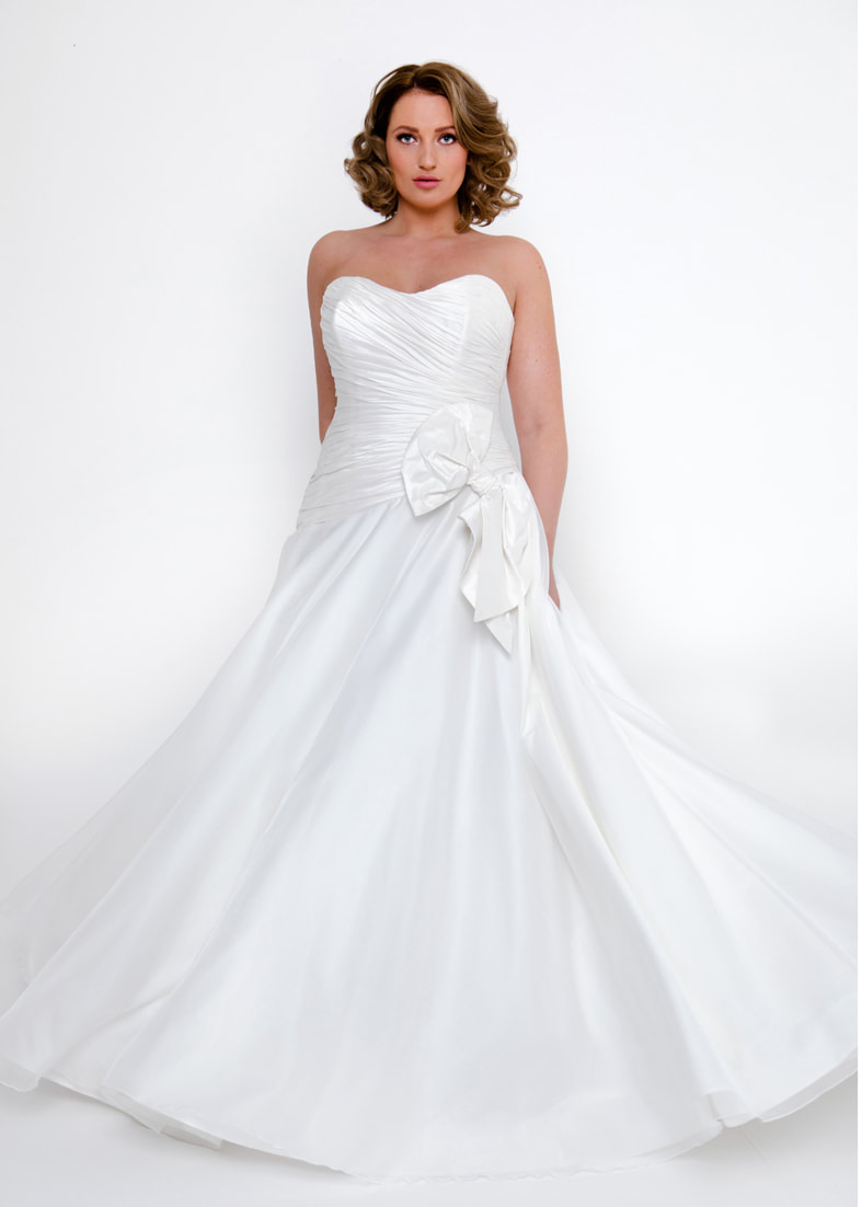 Strapless wedding dres with a full skirt and pleated bodice. Adorned with a large bow detail