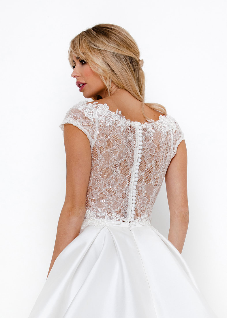 Back fastening bridal shrug in embroidered tulle. Back shot shown with a sheer back, button fastening detail and lace embellished neckline