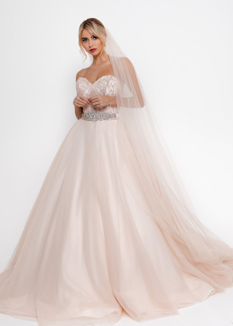 Blush coloured strapless wedding dress with a full tulle ballgown skirt
